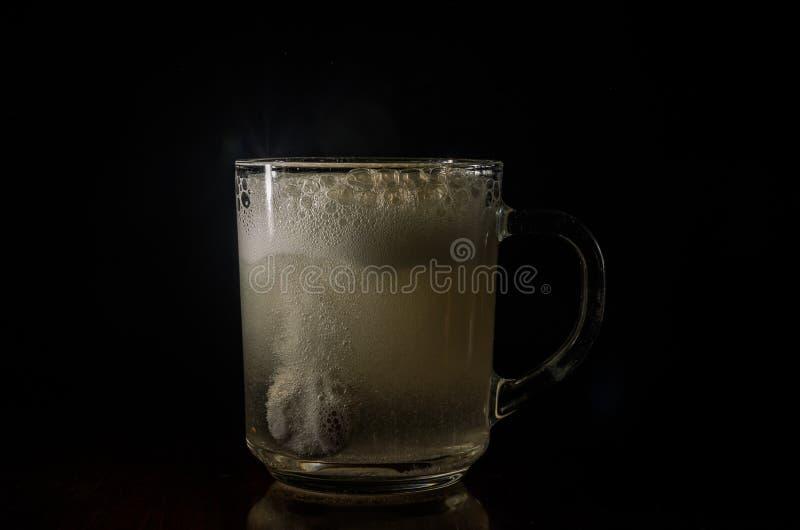 L'homme jette le comprimé effervescent dans l'eau photos stock