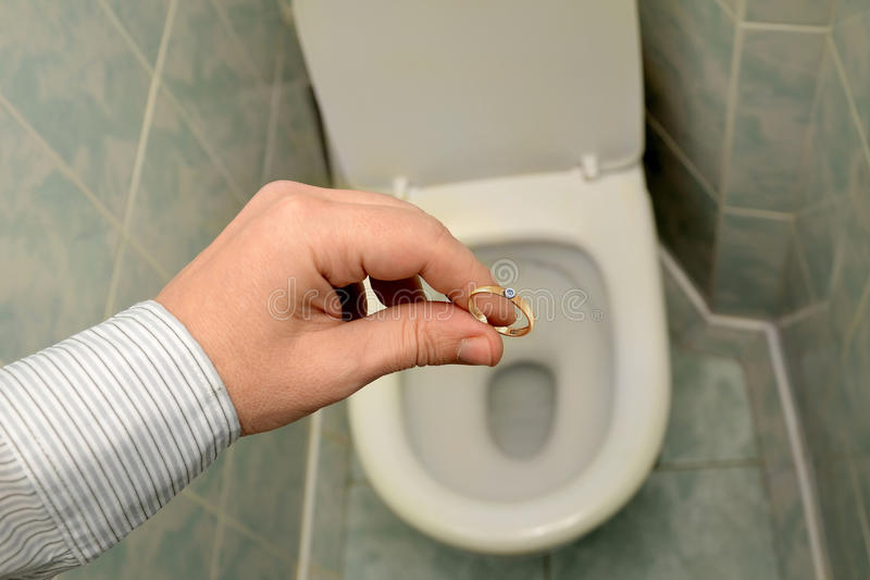 L'homme jette un anneau de mariage dans la toilette Divorce, fin de l'amour photographie stock libre de droits