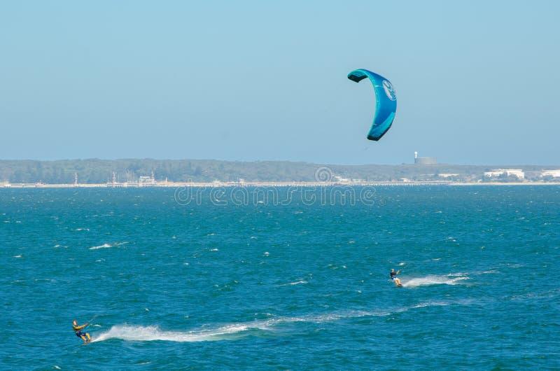 L'homme jouant l'action extrême en sautant au-dessus de l'eau de mer avec le conseil de kitesurf dans la couleur verte à la plage photo libre de droits