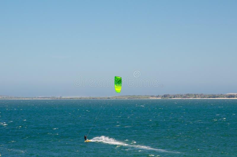 L'homme jouant le kitesurf dans la couleur verte à la plage de Brighton le sands pendant le jour venteux image libre de droits