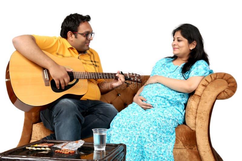 L'homme joue la guitare à son épouse enceinte images stock