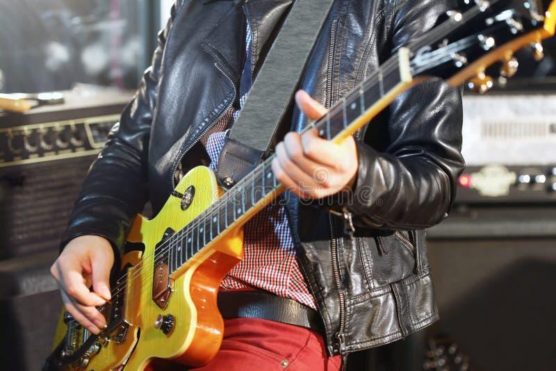 L'homme joue la guitare électrique dans le studio photo libre de droits