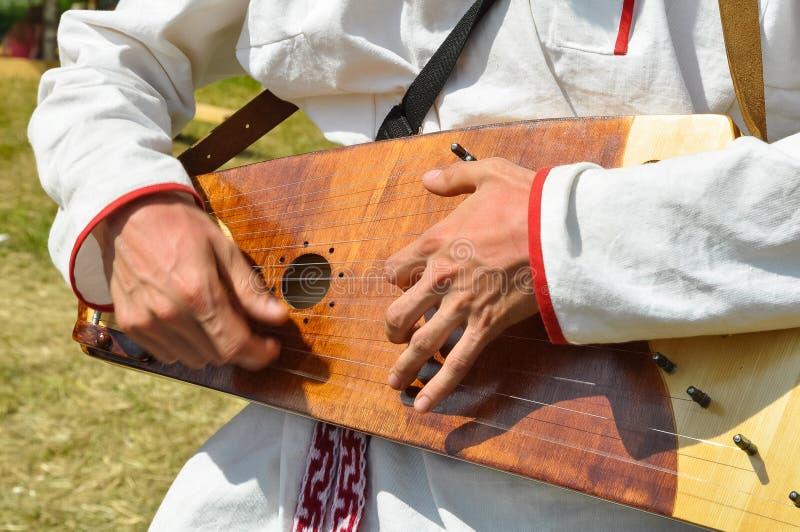L'homme joue un instrument de musique russe traditionnel antique - gusli photo stock