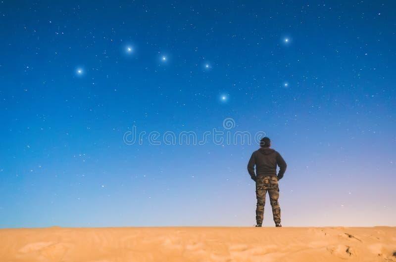 L'homme la nuit dans le ciel étoilé et voit la constellation le grand ours image stock