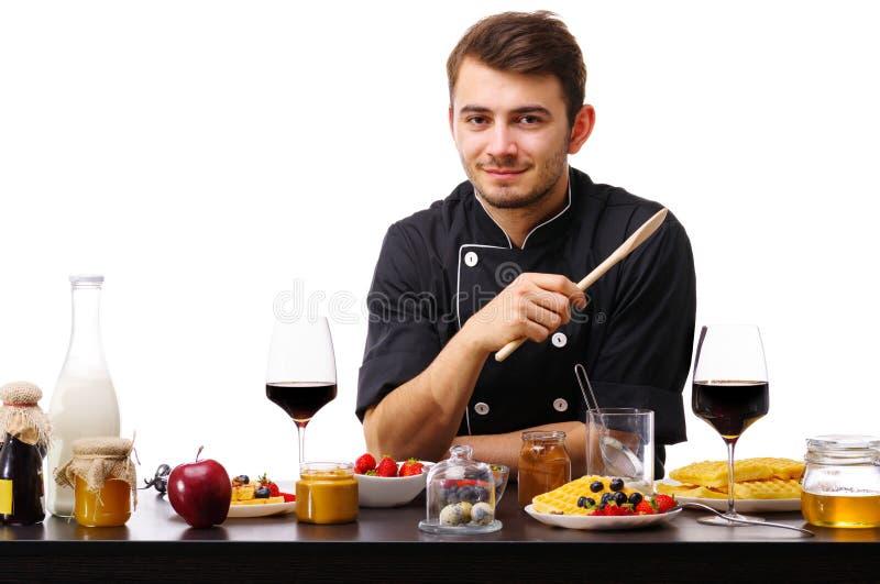 L'homme, le cuisinier, se tient dans la cuisine avec une cuillère en bois, prête à commencer le travail photo libre de droits