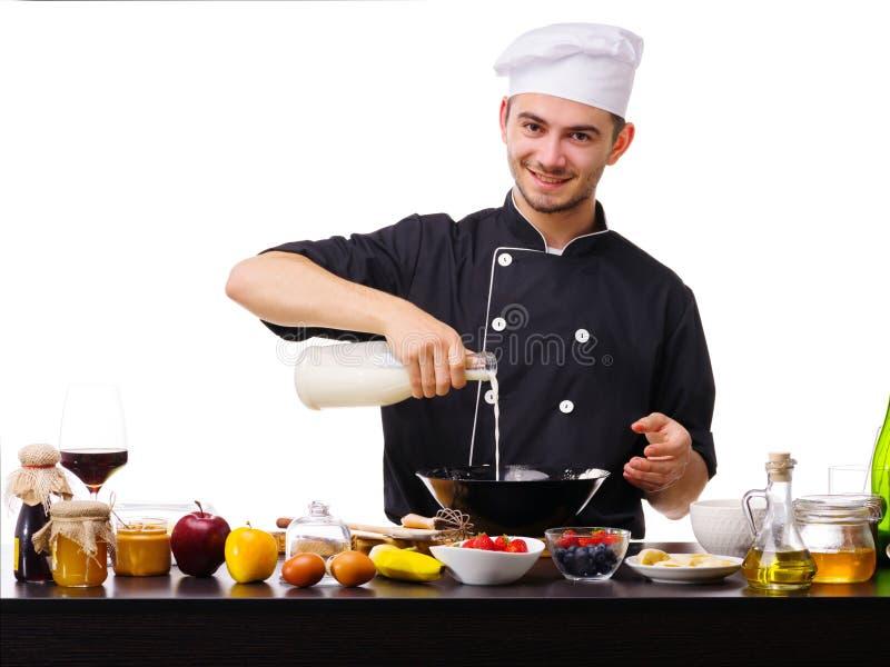 L'homme, le cuisinier, se tient dans la cuisine tout en faisant cuire, versant le lait dans un grand plat noir photo libre de droits