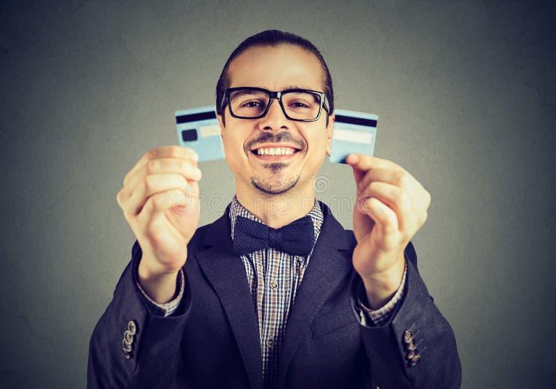 L'homme libre d'affaires de dette enthousiaste en verres tenant une carte de crédit a coupé dans deux morceaux photos libres de droits
