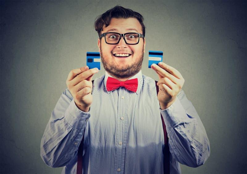 L'homme libre d'affaires de dette enthousiaste en verres tenant une carte de crédit a coupé dans deux morceaux images stock