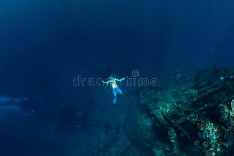 L'homme libre de plongeur dans la profondeur font des bulles d'anneau près du naufrage photo stock