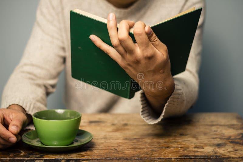 L'homme lit et prend le café photographie stock libre de droits