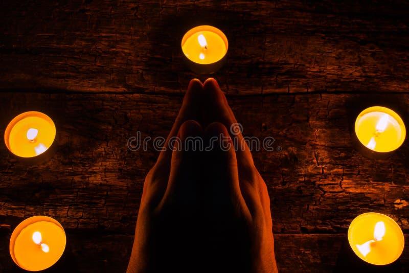 L'homme lit une prière entouré par des bougies images libres de droits