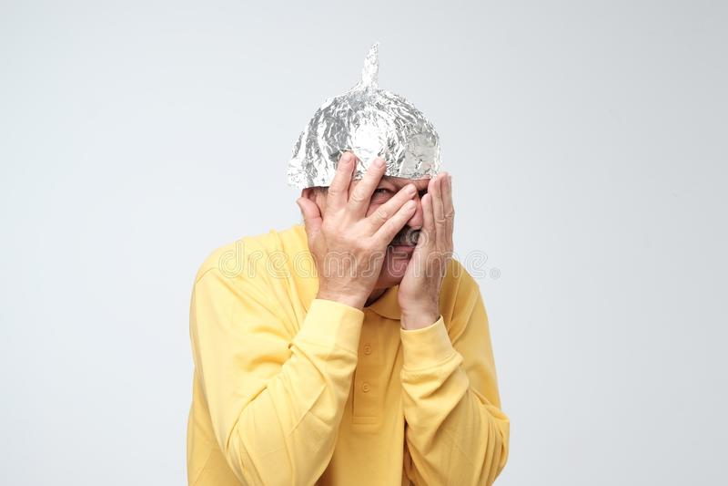 L'homme mûr caucasien dans un chapeau de papier d'aluminium a contrarié fermer son visage avec des mains images libres de droits