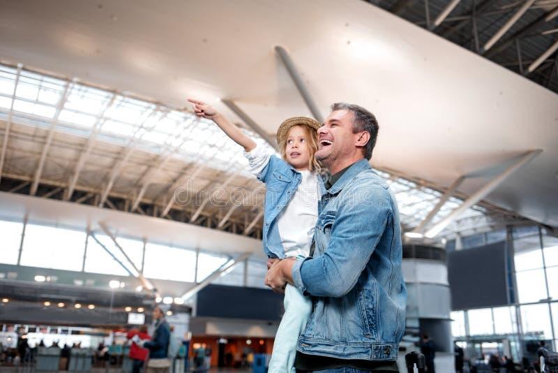 L'homme mûr joyeux tient la petite fille sur le terminal photo stock