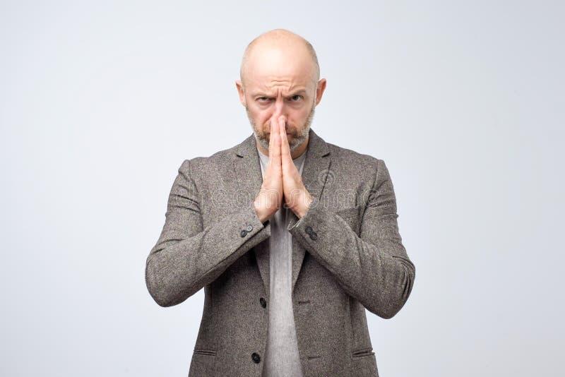 L'homme mûr malheureux dans le costume occasionnel avec prier l'expression, demande la faveur, maintient des mains dans le geste  image stock
