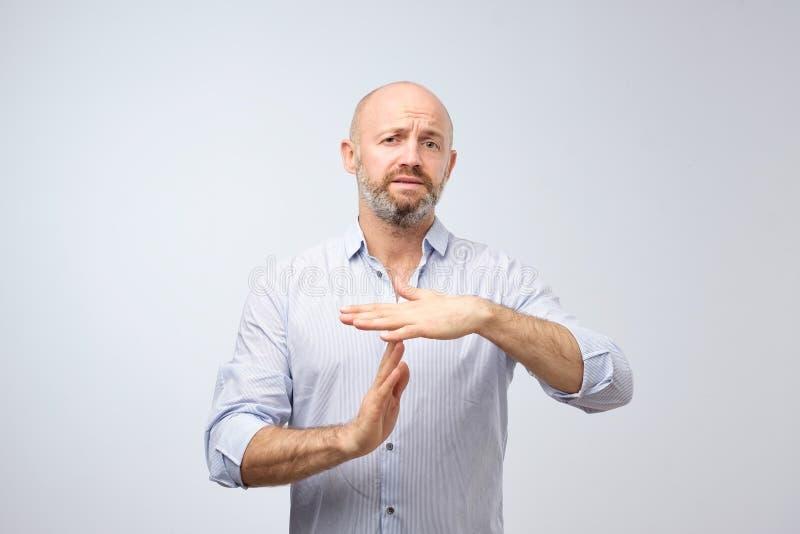 L'homme mûr montrant le geste de main de temps, demandant à s'arrêter a isolé sur le fond gris de mur photo stock