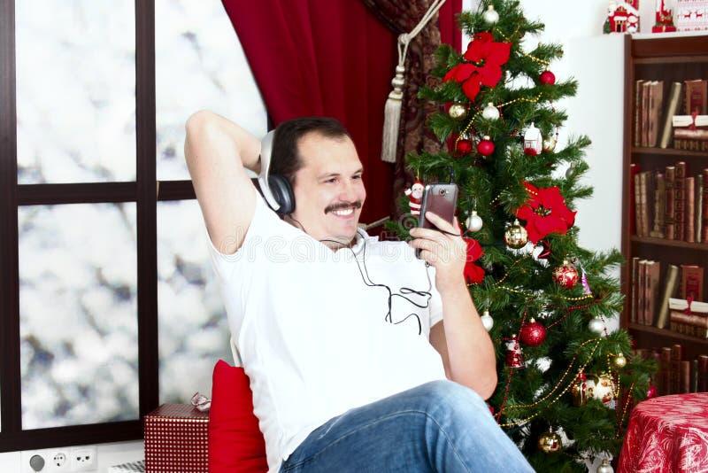 L'homme mûr écoutant la musique sur des écouteurs s'approchent de l'arbre de Noël images stock