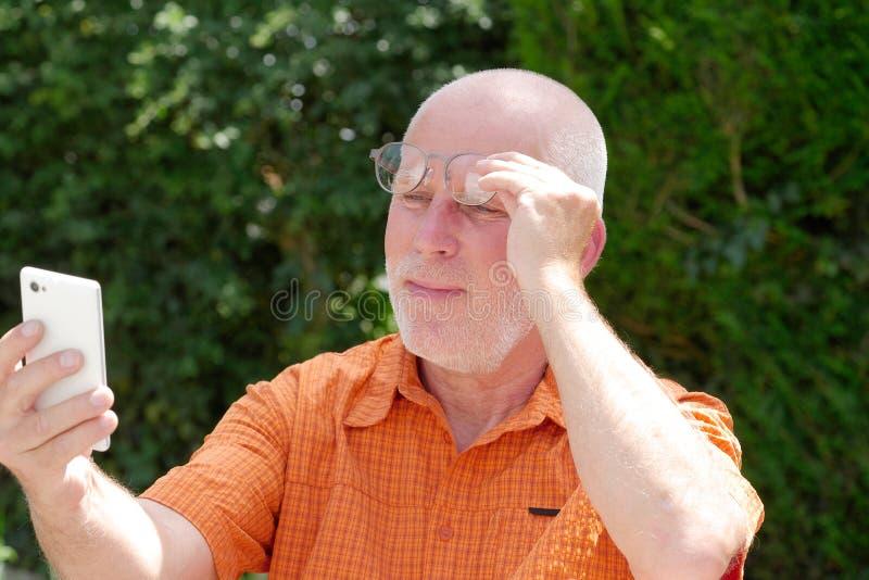 L'homme mûr a des problèmes avec sa vue pour lire sur son sma photos libres de droits