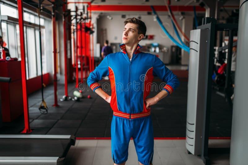 L'homme maigre dans les vêtements de sport montre ses
