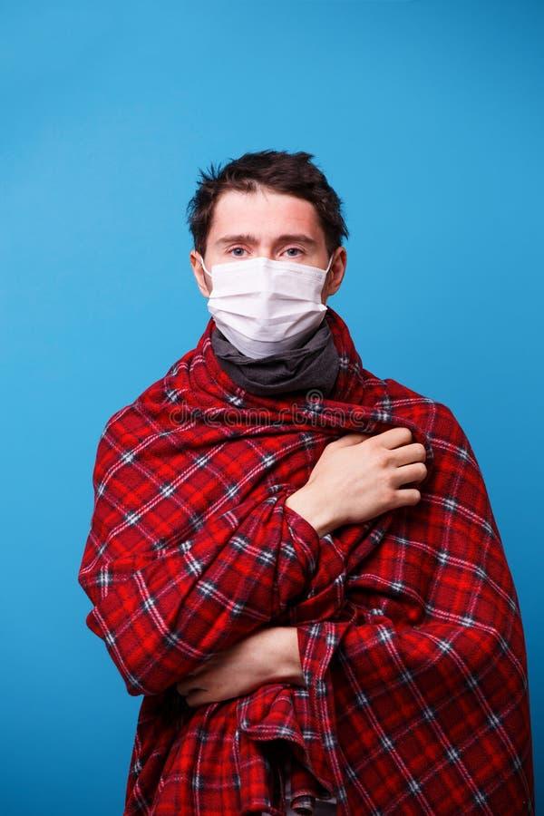 L'homme malade dans le masque enveloppé dans une couverture se tient sur un fond bleu photographie stock