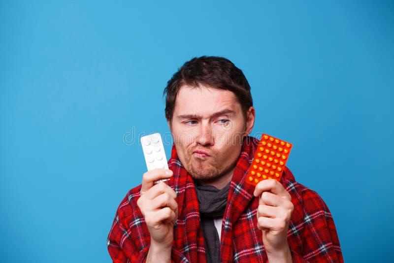 L'homme malade enveloppé dans une couverture choisit des pilules image libre de droits