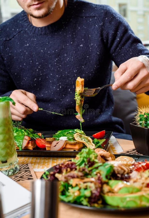 L'homme mange des gaufres avec du jambon, le fromage, des oeufs, des tomates et la sauce à épinards et boit un smoothie vert dans image libre de droits