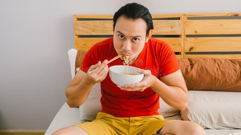 L'homme mange des nouilles image stock