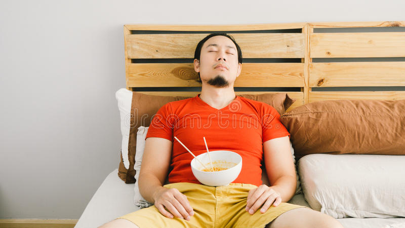 L'homme mange des nouilles photos stock