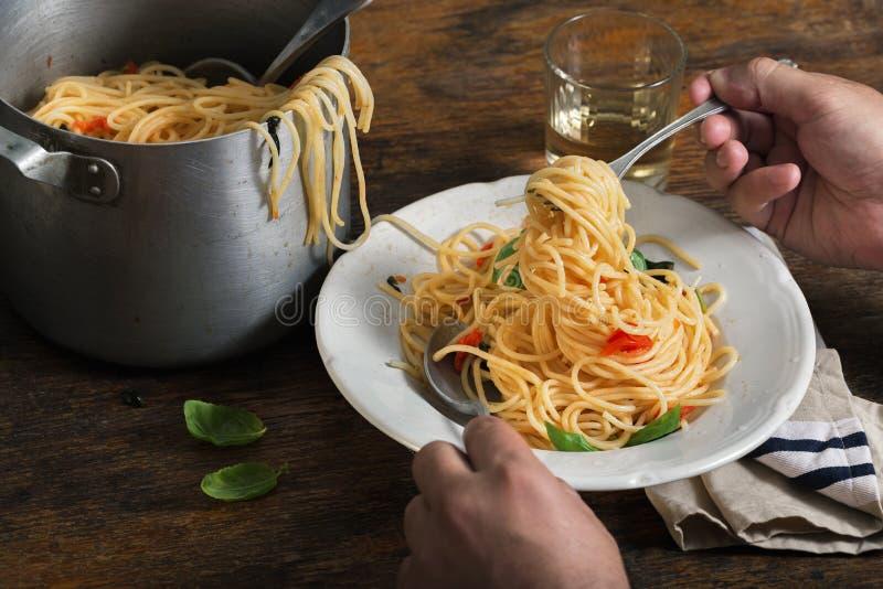 L'homme mange des pâtes italiennes sur une table en bois rustique photos libres de droits