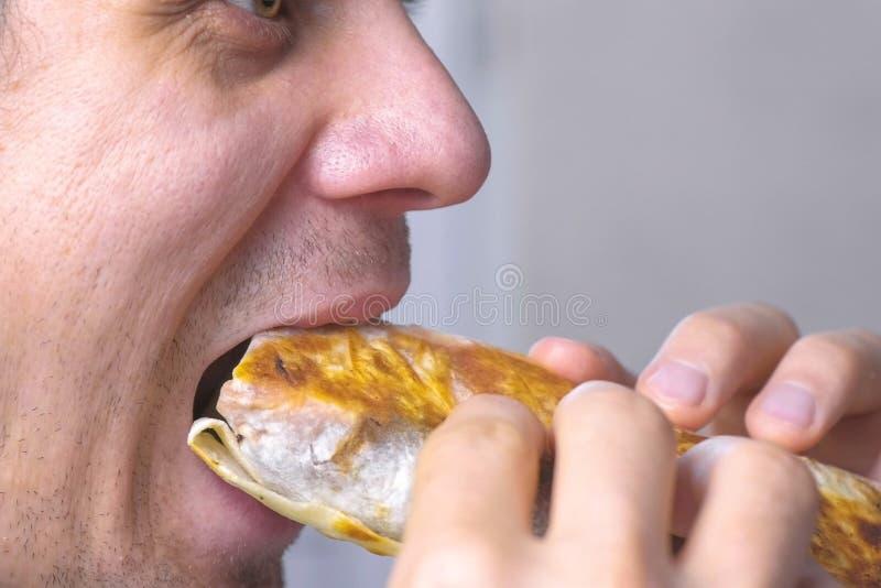 L'homme mange le shawarma fait maison de poulet savoureux photos libres de droits