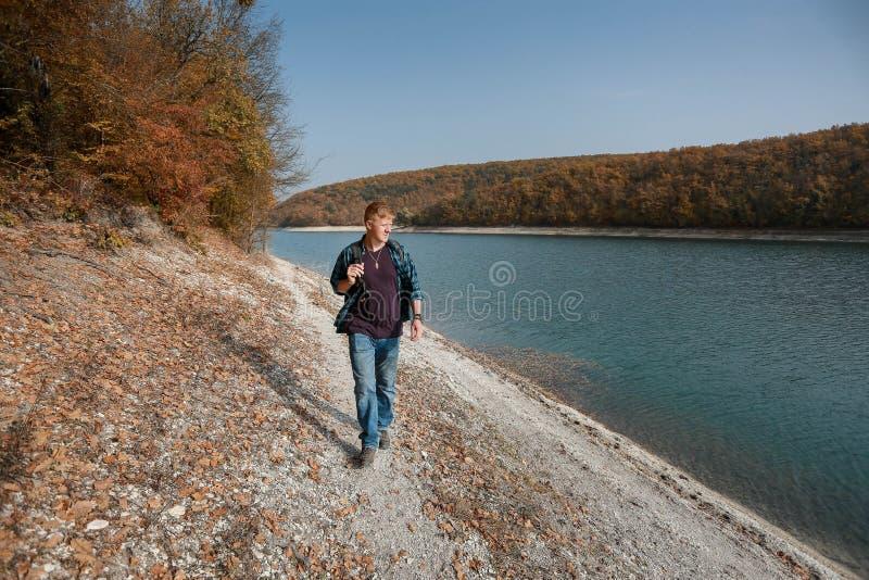 L'homme marche près du lac en automne image stock