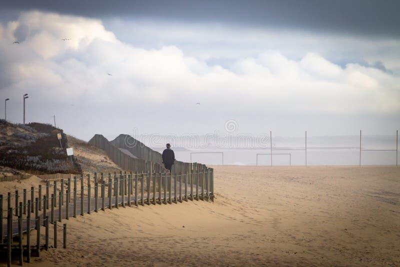 L'homme marche sur la promenade à la plage photographie stock