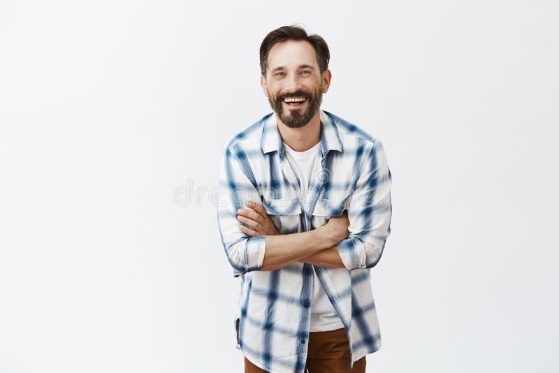 L'homme masculin bel adulte avec la barbe et la moustache, riant, se tenant remet croisé et souriant largement, ayant photos libres de droits