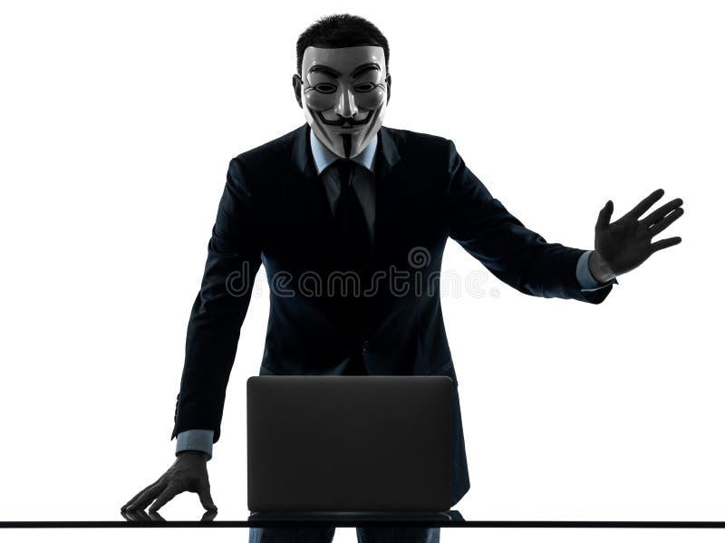 L'homme a masqué l'ordinateur de calcul de membre anonyme de groupe saluant le SI photographie stock