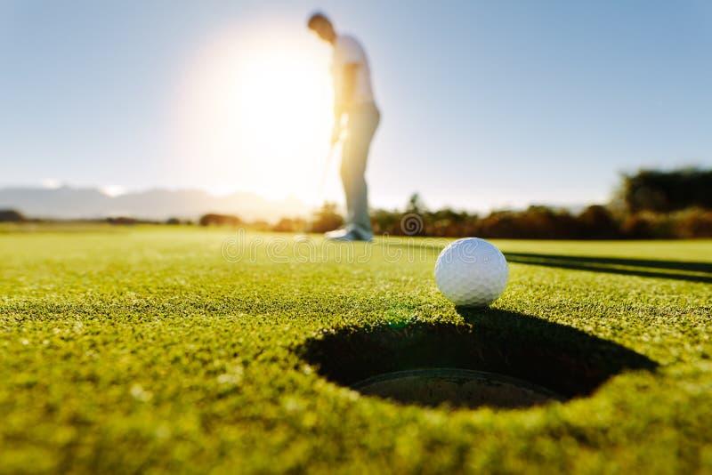 L'homme met la boule sur le vert de terrain de golf photo libre de droits