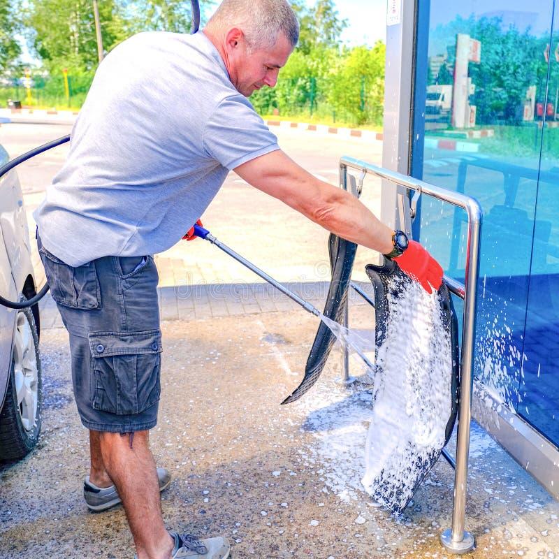 L'homme met la mousse active sur le tapis de voiture Machine propre de Washington de v?hicule, lavage de voiture avec l'?ponge et photo libre de droits
