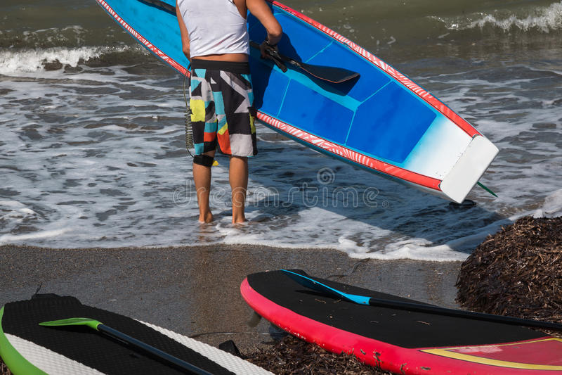L'homme a mis le conseil dans l'eau dans Shoreline image stock