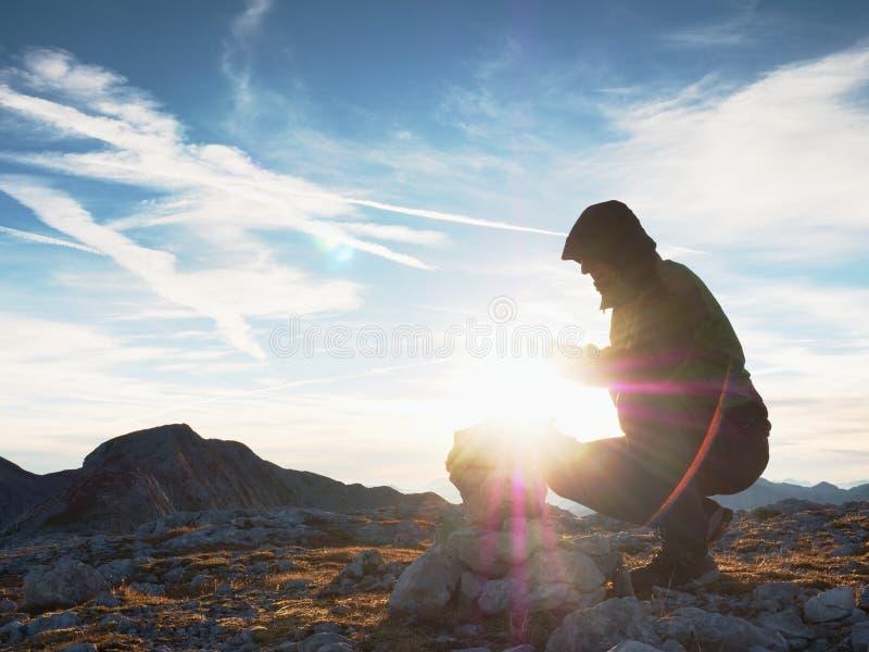 L'homme a mis le dernier intopeak en pierre de la pyramide Pyramide en pierre équilibrée sur le sommet de montagne image stock