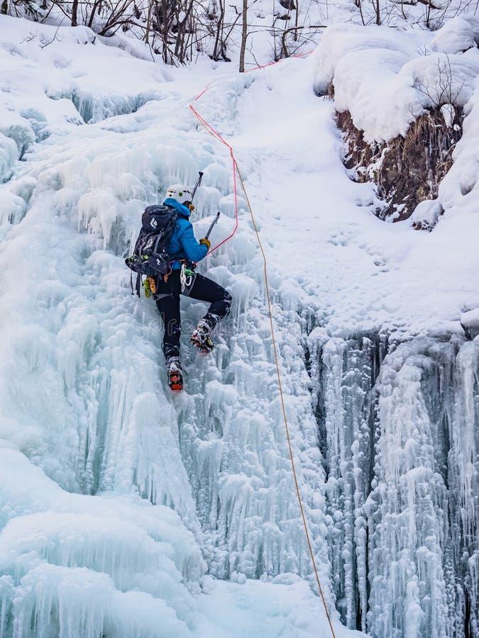 L'homme montant la cascade congelée photographie stock libre de droits