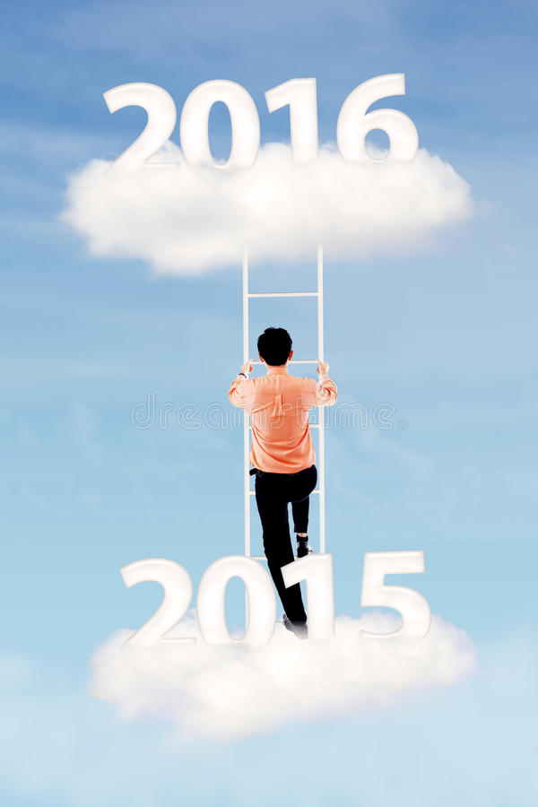 L'homme monte l'échelle avec des numéros 2015 et 2016 photographie stock libre de droits