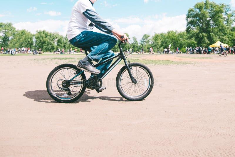 L'homme monte un petit vélo de montagne un jour ensoleillé d'été Promenade autour du parc sur un vélo Homme adulte sur un vélo d' image stock