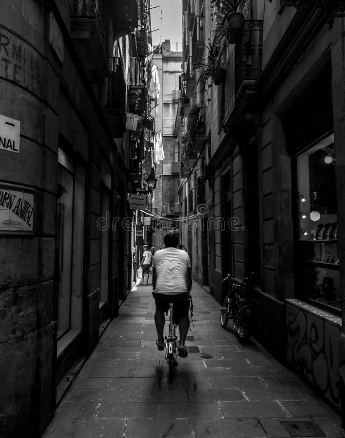 L'homme monte une bicyclette le long des rues serrées de Barcelone photographie stock