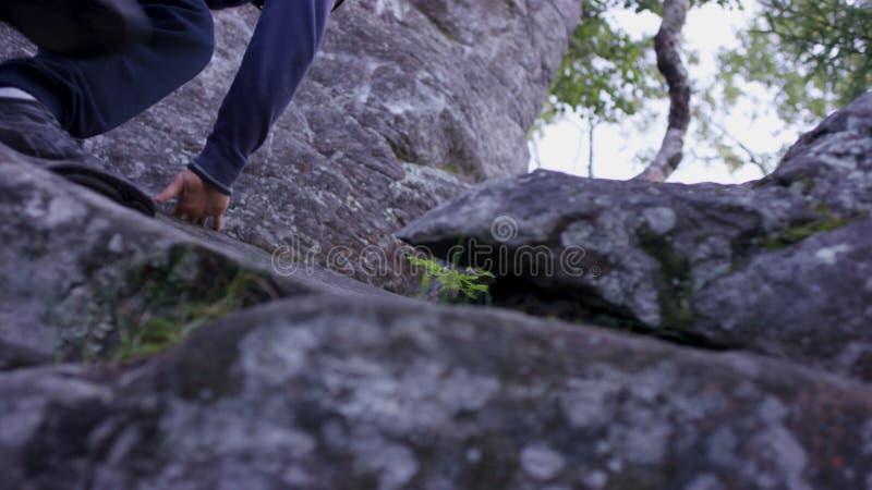 L'homme monte une roche de surplomb près de la forêt et les poignées se tiennent Athlète sur les roches dans la forêt, mode de vi image libre de droits