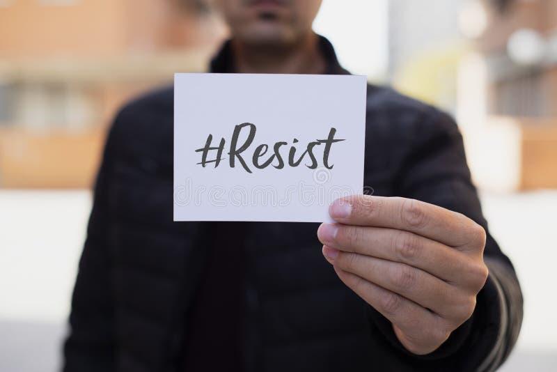 L'homme montrant une note avec le hashtag résistent photos libres de droits
