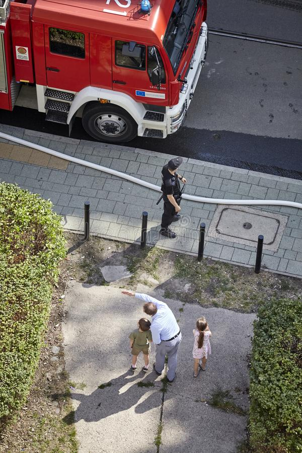 L'homme montre à des enfants des sapeurs-pompiers qui disposent à s'éteindre le feu image stock