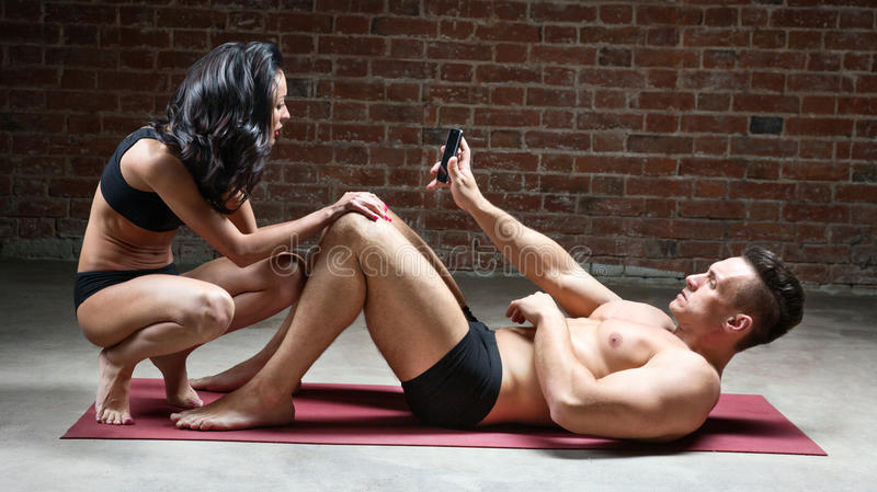 L'homme montre à fille son téléphone tout en se trouvant sur un tapis photo stock