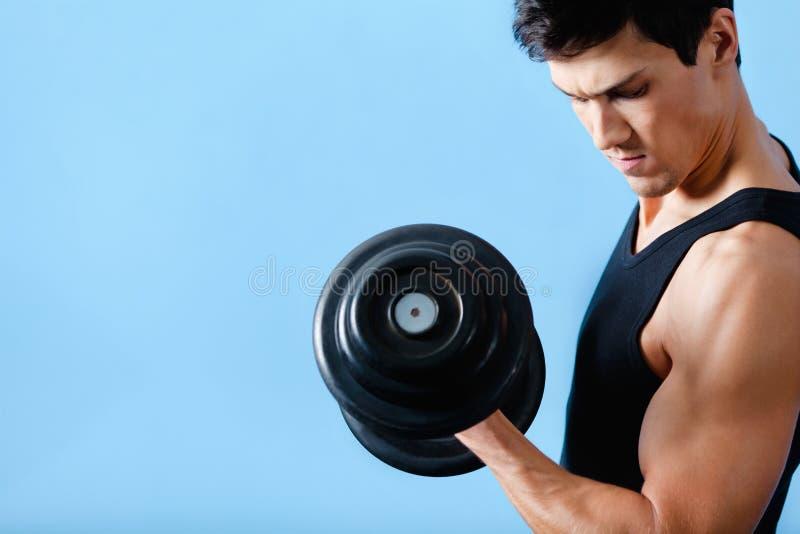 L'homme musculaire bel utilise son haltère photo libre de droits