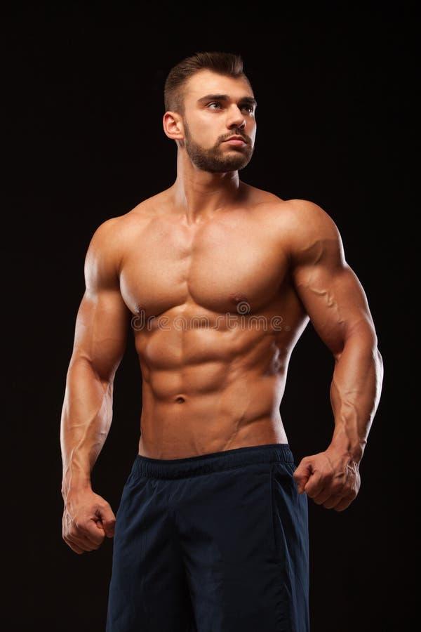 L'homme musculaire de forme physique est posant et montrant son torse avec six ABS de paquet D'isolement sur le fond noir avec Co photo stock