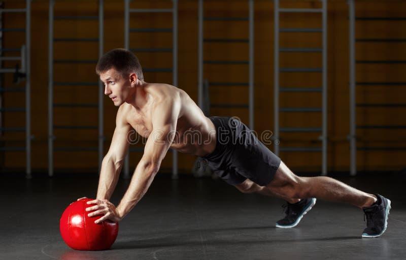 L'homme musculaire faisant le sport s'exerce avec le medicine-ball rouge photographie stock