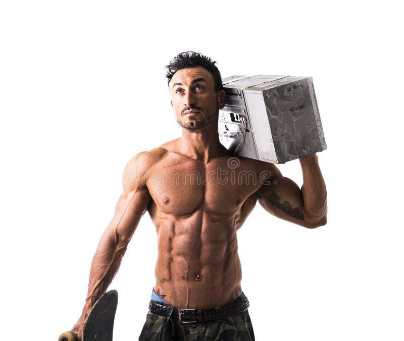L'homme musculaire sans chemise avec la planche à roulettes et le boombox transmettent par radio photo libre de droits