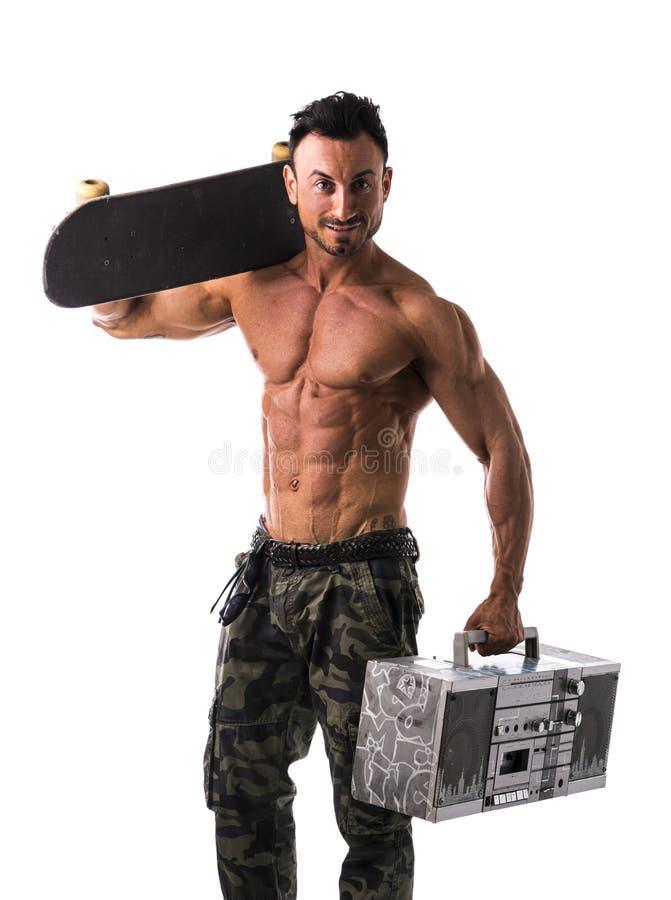 L'homme musculaire sans chemise avec la planche à roulettes et le boombox transmettent par radio image libre de droits